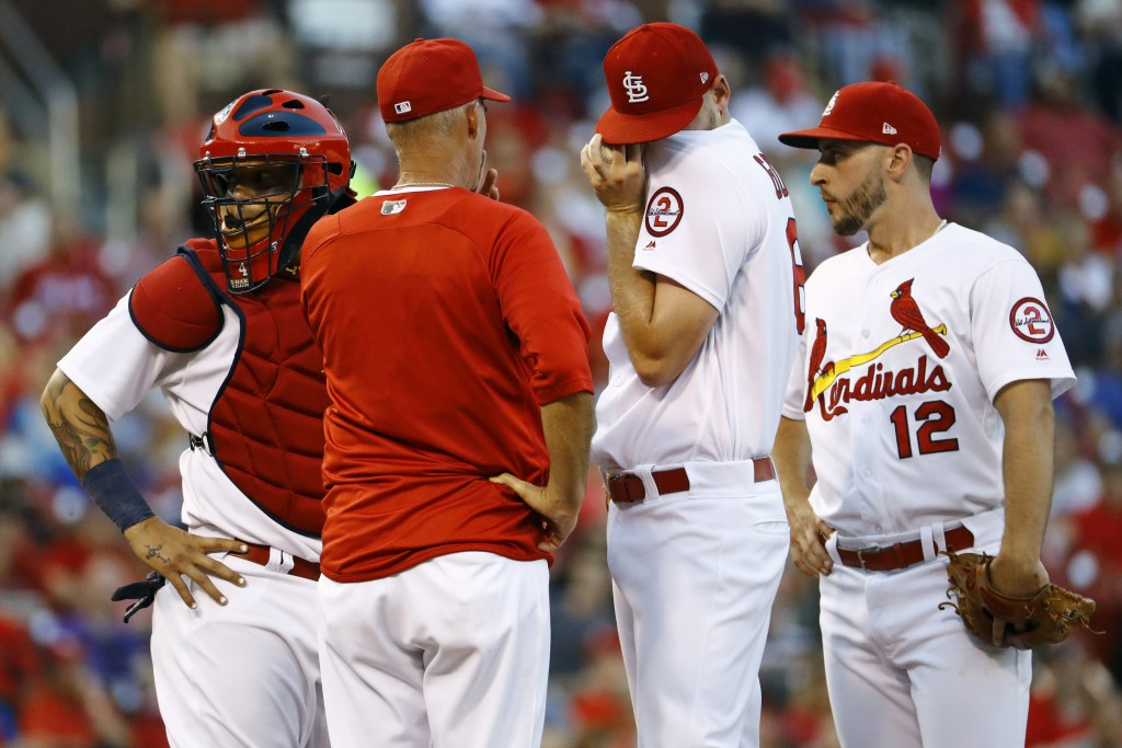 St. Louis Cardinals starting pitcher Austin Gomber, second from right, speaks with pitching coach Mike Maddux, second from left, as catcher Yadier Mol