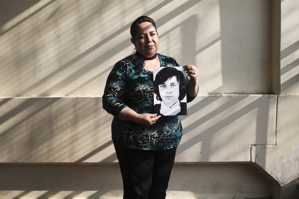 In this Thursday, Sept. 6, 2018 photo, 54-year-old teacher Vittoria E Natto poses for a portrait inside her high school holding a photo of herself whe