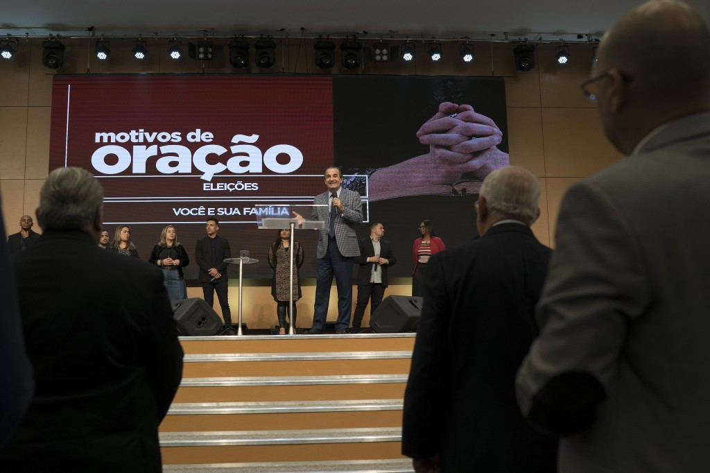 "In this Sept. 2, 2018 photo, pastor Silas Malafaia delivers a sermon backdropped by a screen with a message that reads in Portuguese: "" Reasons to pra"