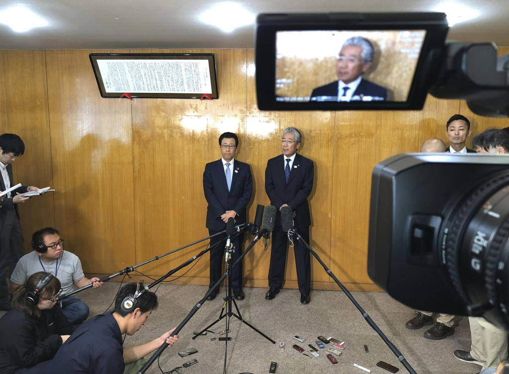 FILE - In this May 14, 2018, file photo, Sapporo Mayor Katsuhiro Akimoto, center left, and Tsunekazu Takeda, center right, an IOC member and head of t