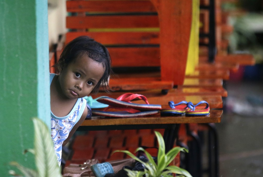 A girl looks outs from her room at a temporary evacuation center in Cagayan province, northeastern Philippines on Friday, Sept. 14, 2018. Typhoon Mang...