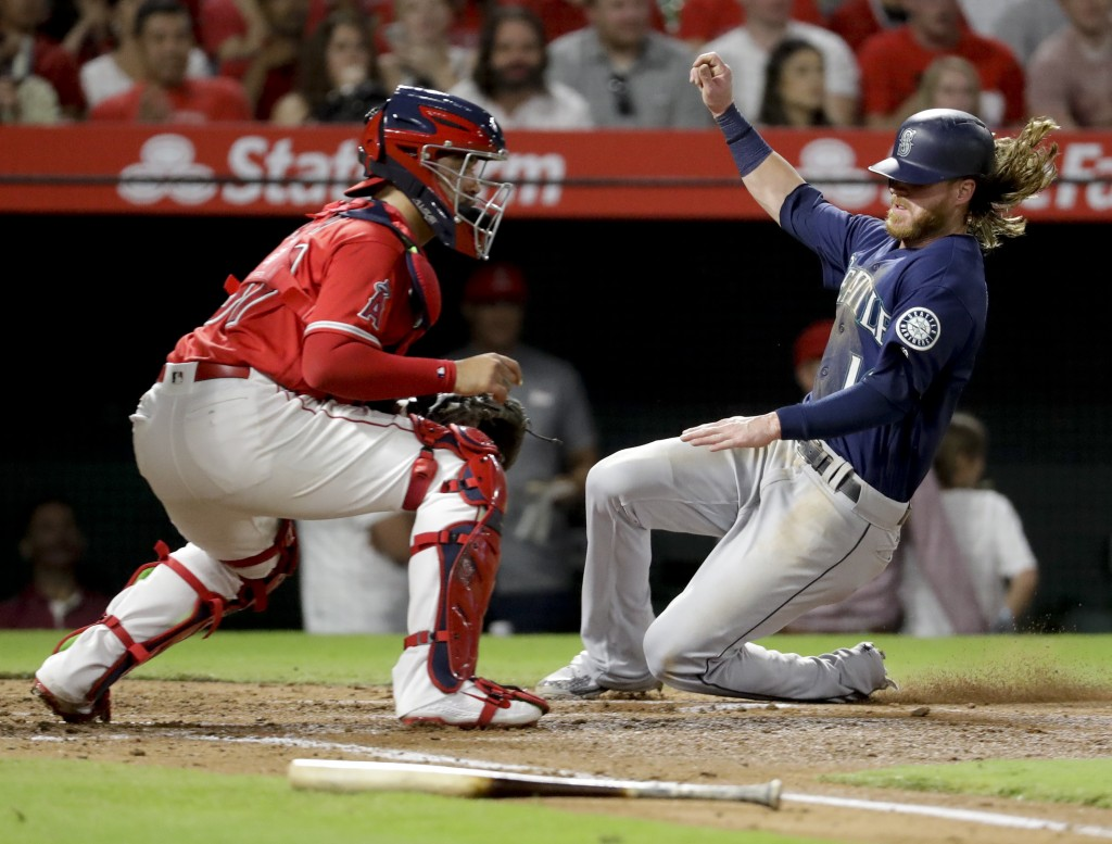 Seattle Mariners' Ben Gamel scores past Los Angeles Angels third baseman Jefry Marte on a sacrifice fly by Dee Gordon during the second inning of a ba