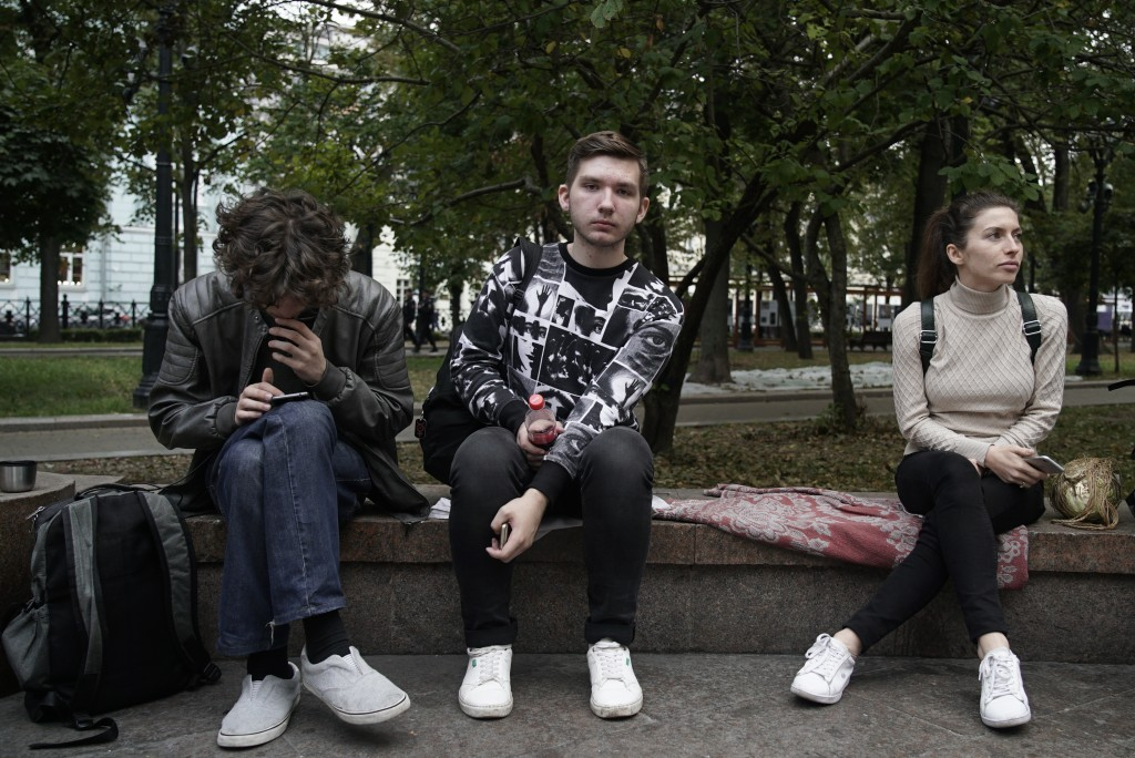 In this photo taken on Monday, Sept. 10, 2018, high school student Viktor, center, and a theater student Andrei Zabara, left, sit in a park in Moscow,