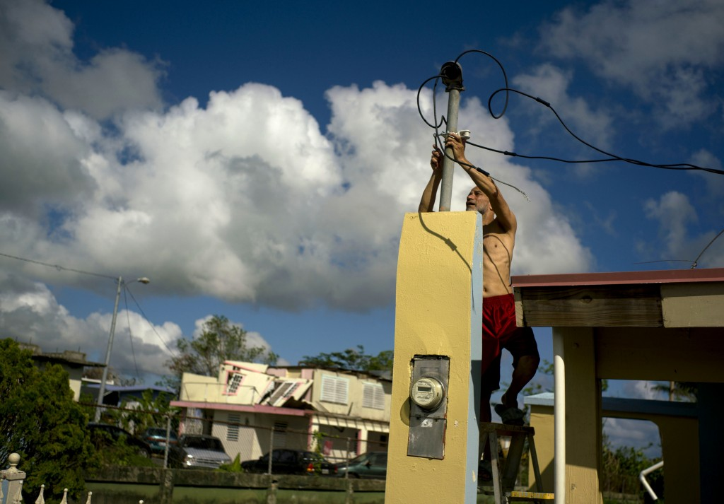 FILE - In this Oct. 13, 2017 file photo, a resident tries to connect electrical lines downed by Hurricane Maria in preparation for when electricity is