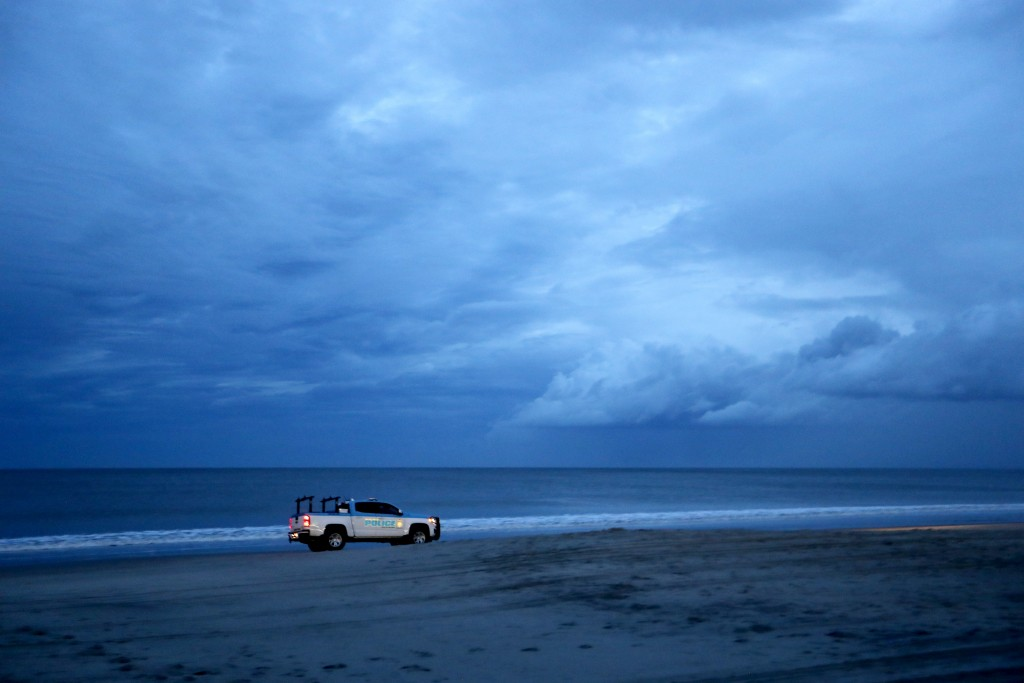 A police vehicle patrols the beach after an evening curfew went into effect as Hurricane Florence approaches Myrtle Beach, S.C., Thursday, Sept. 13, 2