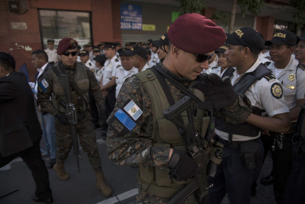 In this Sept. 12, 2018 photo, soldiers and police stand guard near the congress building as Guatemalan President Jimmy Morales attends a session to ce