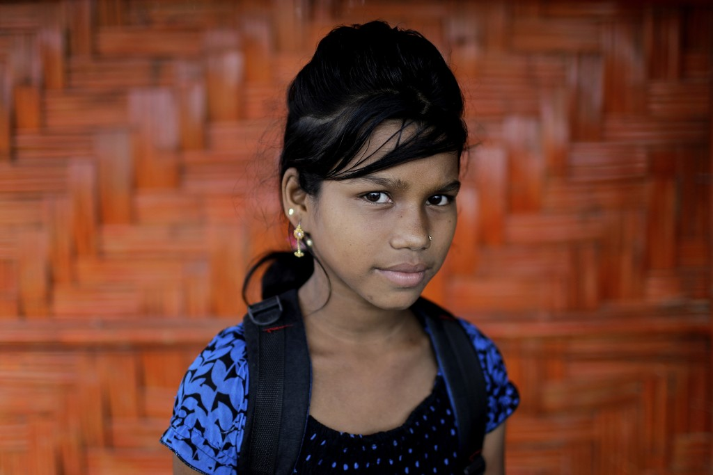 In this June 27, 2018, photo, Astafa, 10, poses for a portrait in front of her classroom in Chakmarkul refugee camp, Bangladesh. Amid the misery and m