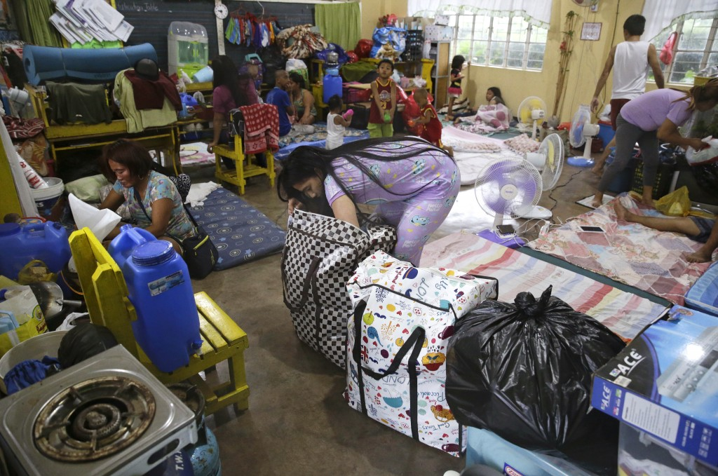 An evacuee fixes her bag inside a temporary evacuation center at Tuguegarao city, Cagayan province, northeastern Philippines on Friday, Sept. 14, 2018
