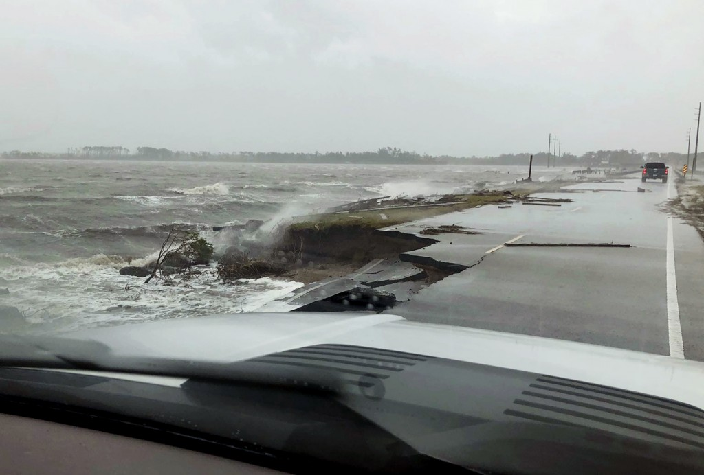 In this photo provided by Jordan Guthrie, wind and water from Hurricane Florence damages the highway leading off Harkers Island, N.C. on Friday, Sept.
