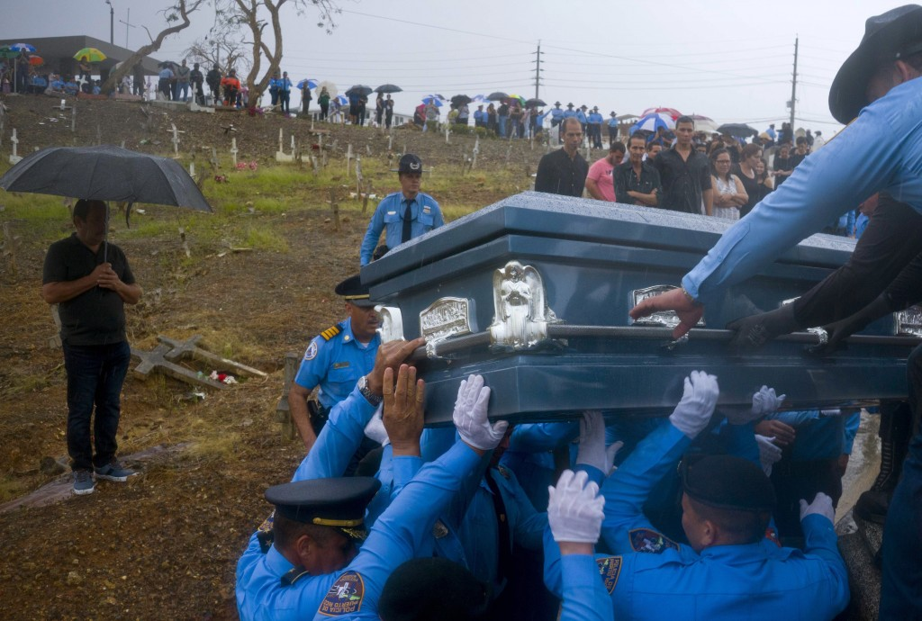 FILE - In this Sept. 29, 2017 file photo, police lift the coffin of fellow officer Luis Angel Gonzalez, during his funeral at the cemetery in Aguada,