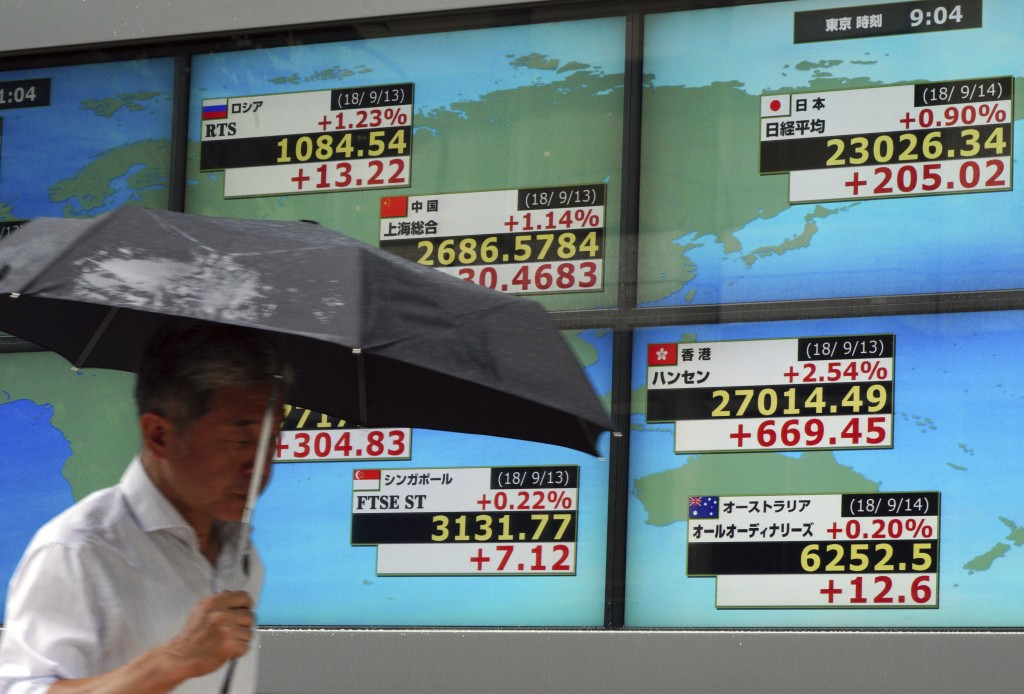 A man walks past an electronic stock board showing Japan's Nikkei 225 index and other contorted indexs at a securities firm in Tokyo Friday, Sept. 14,