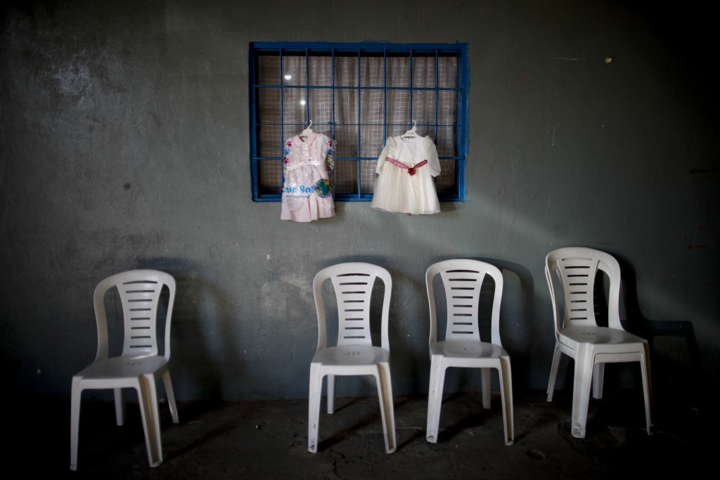 In this Sept. 6, 2018 photo, dresses hang for exchange at a barters market set up by residents inside a community center on the outskirts of Buenos Ai