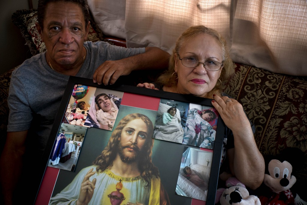 In this Sept. 4, 2018 photo, Maria Gonzalez Munoz, right, and Juan Manuel Gonzalez, pose with an image of Jesus surrounded by photos of her sister Ram