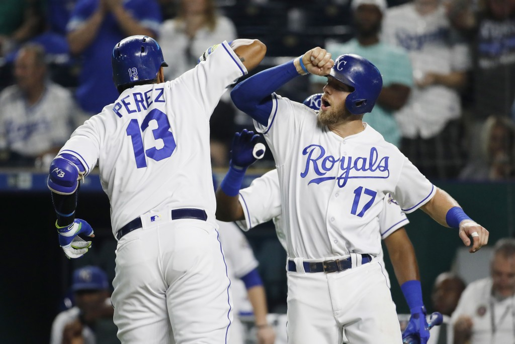 Kansas City Royals' Salvador Perez (13) is congratulated at home plate by Hunter Dozier (17) after hitting a two-run home run in the sixth inning of a