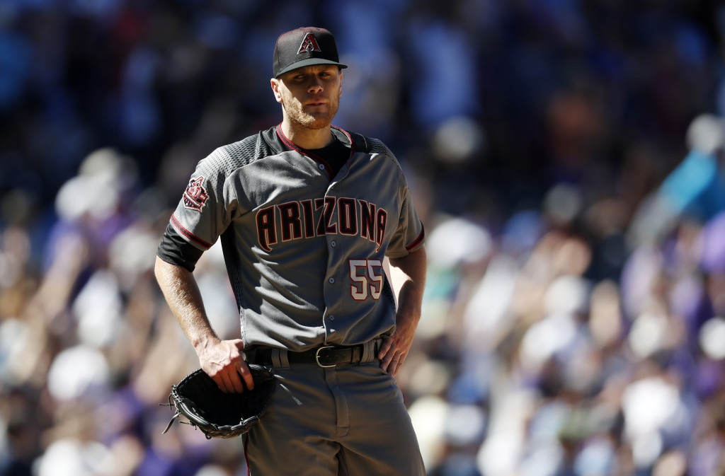 Arizona Diamondbacks starting pitcher Matt Koch reacts after giving up a two-run home run to Colorado Rockies' Trevor Story in the third inning of a b