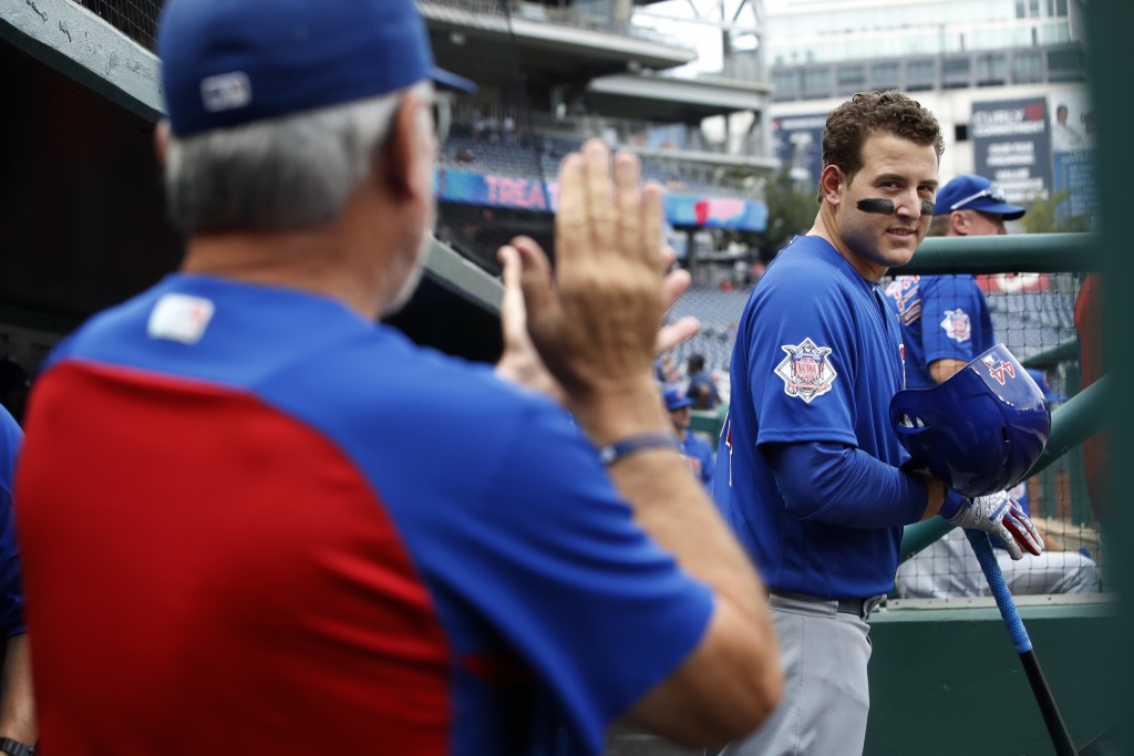 Chicago Cubs first baseman Anthony Rizzo (44) looks at manager Joe Maddon, left, as Maddon claps for the team at the start of a baseball game against