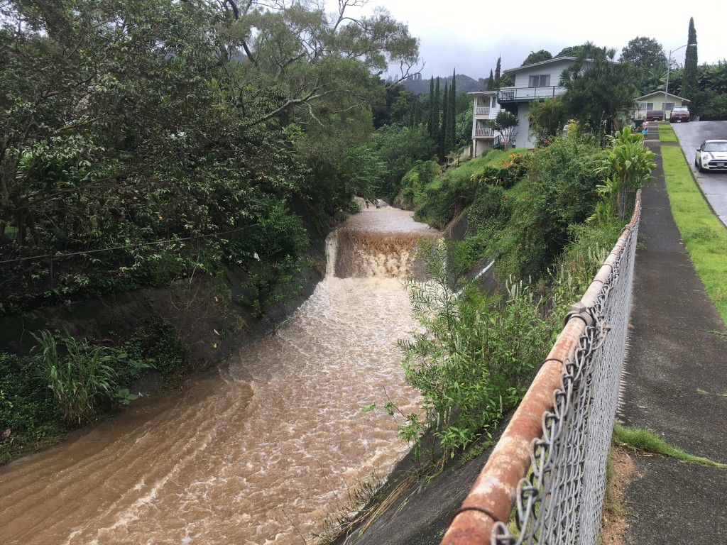 Water is seen rushing through a spillway in a neighborhood below the Nuuanu Dam in Honolulu on Thursday, Sept. 13, 2018. Honolulu officials say they m