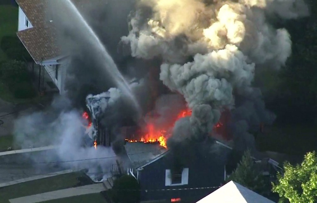 In this image take from video provided by WCVB in Boston, flames consume the roof of a home in Lawrence, Mass, a suburb of Boston, Thursday, Sept. 13,