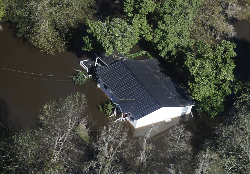 FILE-In this Monday, Oct. 10, 2016 file photo, a home sits in flood waters in Nichols, S.C. The residents of a tiny town in South Carolina who rebuilt