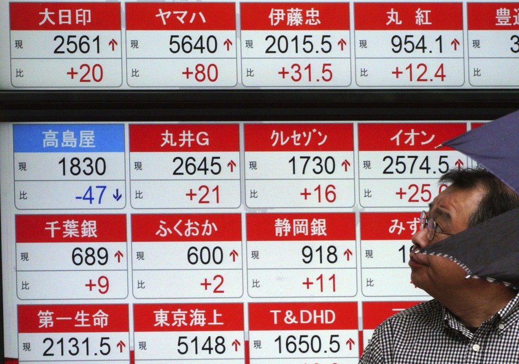 A man looks atan electronic stock board showing Japan's Nikkei 225 index at a securities firm in Tokyo Friday, Sept. 14, 2018. Asian shares were mostl