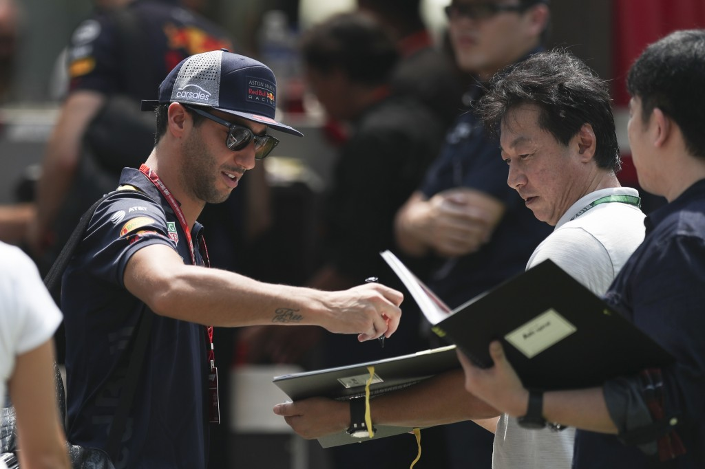 Red Bull Racing driver Daniel Ricciardo of Australia, left, sign autograph as he arrives at the Marina Bay City Circuit ahead of the Singapore Formula...