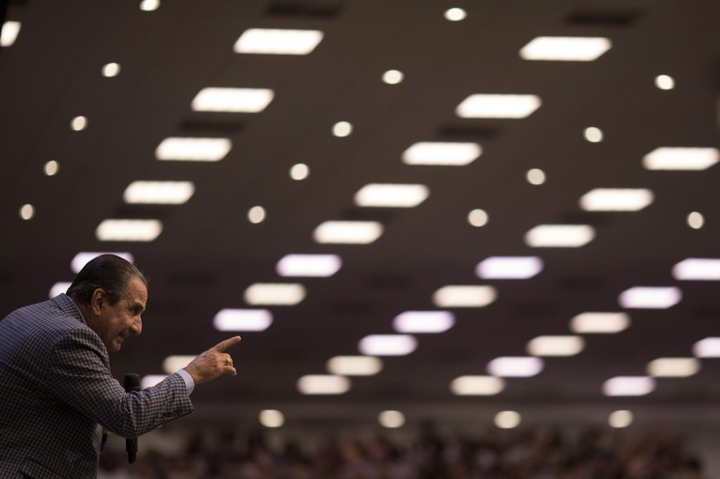 In this Sept. 2, 2018 photo, pastor Silas Malafaia points to his congregants during a service at the Assembly of God Victory in Christ Church, in Rio