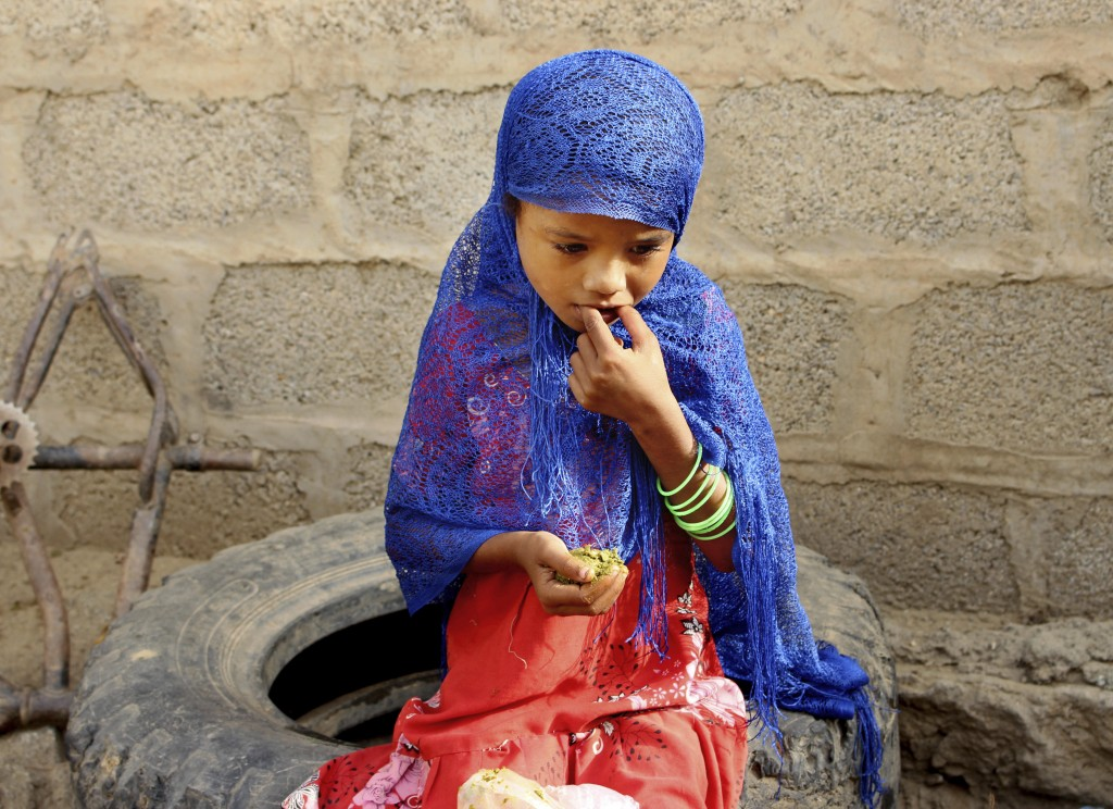 In this Aug. 25, 2018 photo, a girl eats boiled leaves from a local vine to stave off starvation, in the extremely impoverished district of Aslam, Haj...