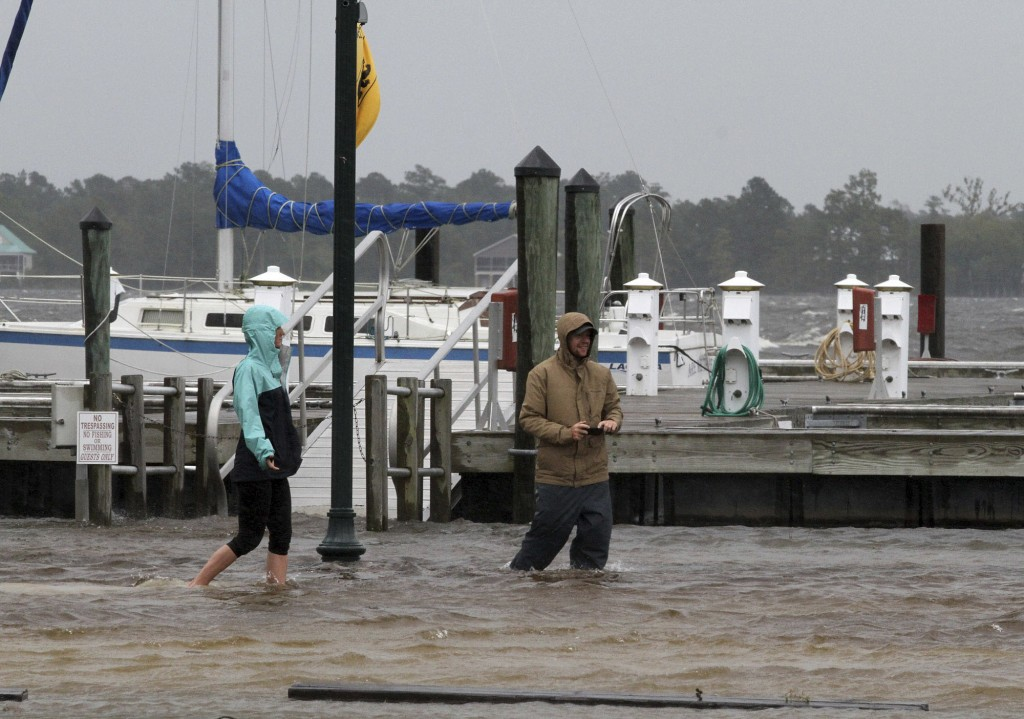 Jamie Thompson and Ryan Thompson walk through flooded areas along the Neuse River near East Front Street in New Bern, N.C. Thursday, Sept. 13, 2018. H