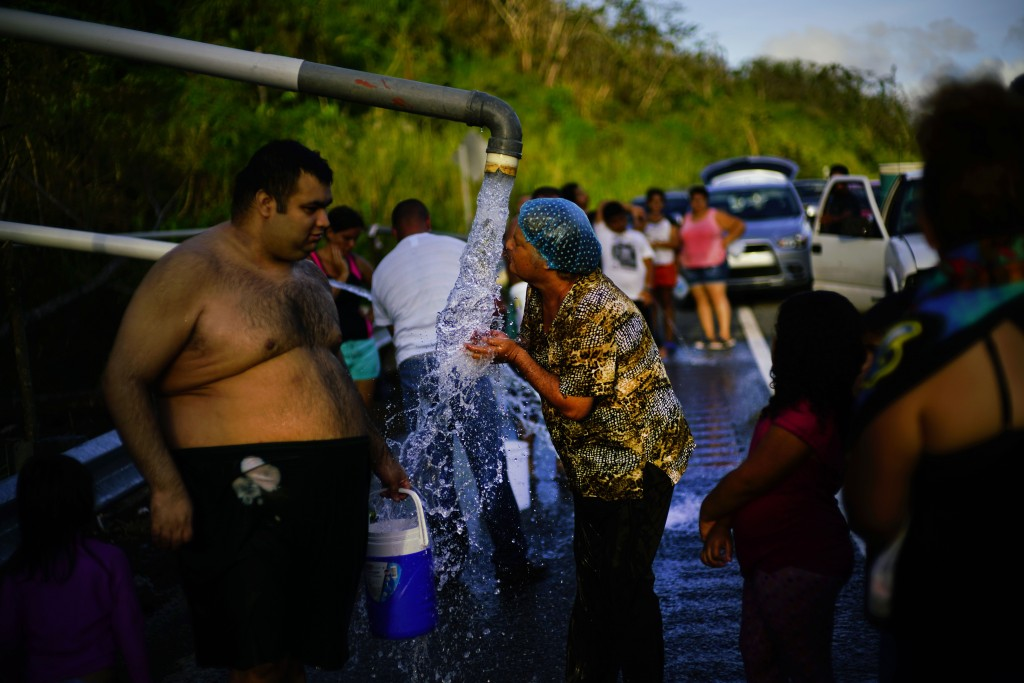 FILE - In this Oct. 14, 2017 file photo, people who lost access to water in the wake of Hurricane Maria gather at pipes carrying water from a mountain