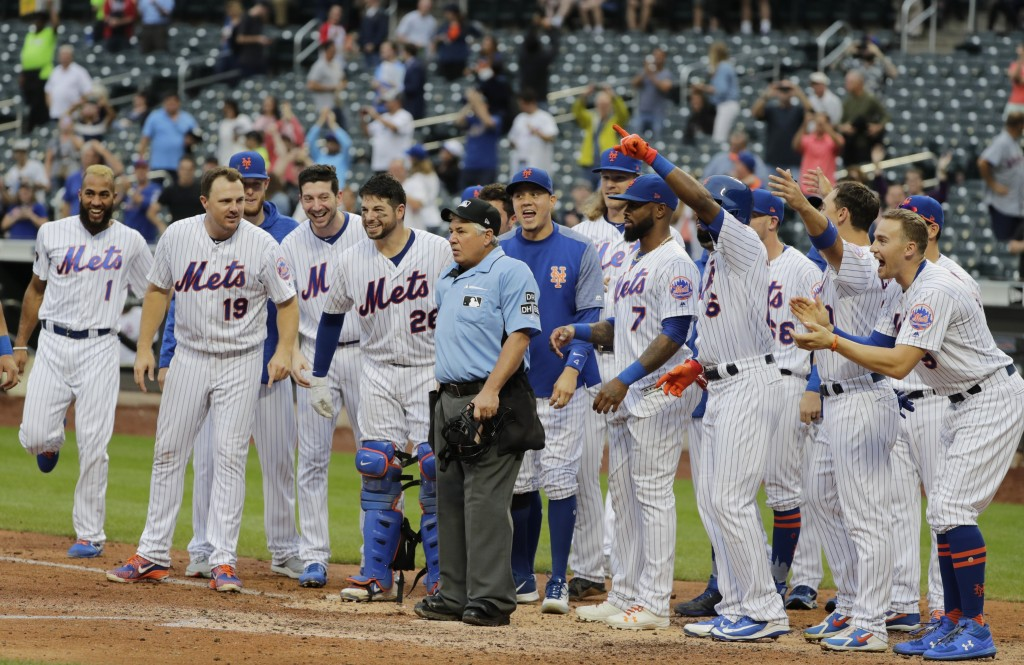 New York Mets players wait for teammate Todd Frazier to arrive at home plate after hitting a walkoff home run during the ninth inning of the first bas