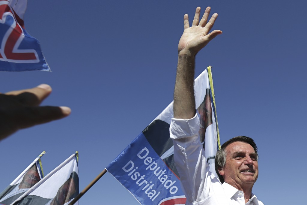 FILE - In this Sept. 5, 2018 file photo, Jair Bolsonaro, National Social Liberal Party presidential candidate, greets supporters during a campaign ral