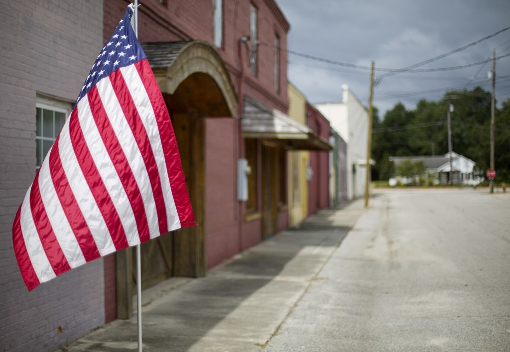 An American flag flies outside a row of vacant stores damaged from Hurricane Matthew's flooding two years ago in Nichols, S.C., Thursday, Sept. 13, 20