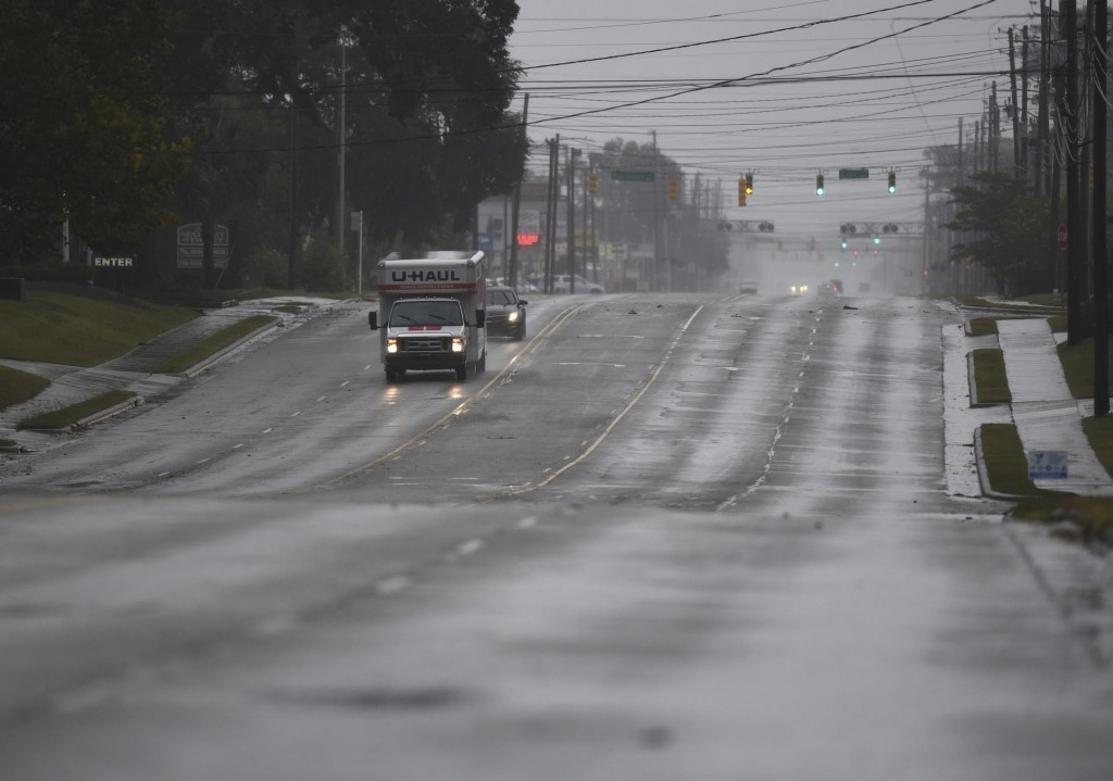A few cars drive along an almost deserted Market St. in Wilmington, N.C., Thursday, Sept. 13, 2018. Florence's outer bands of wind and rain began lash...