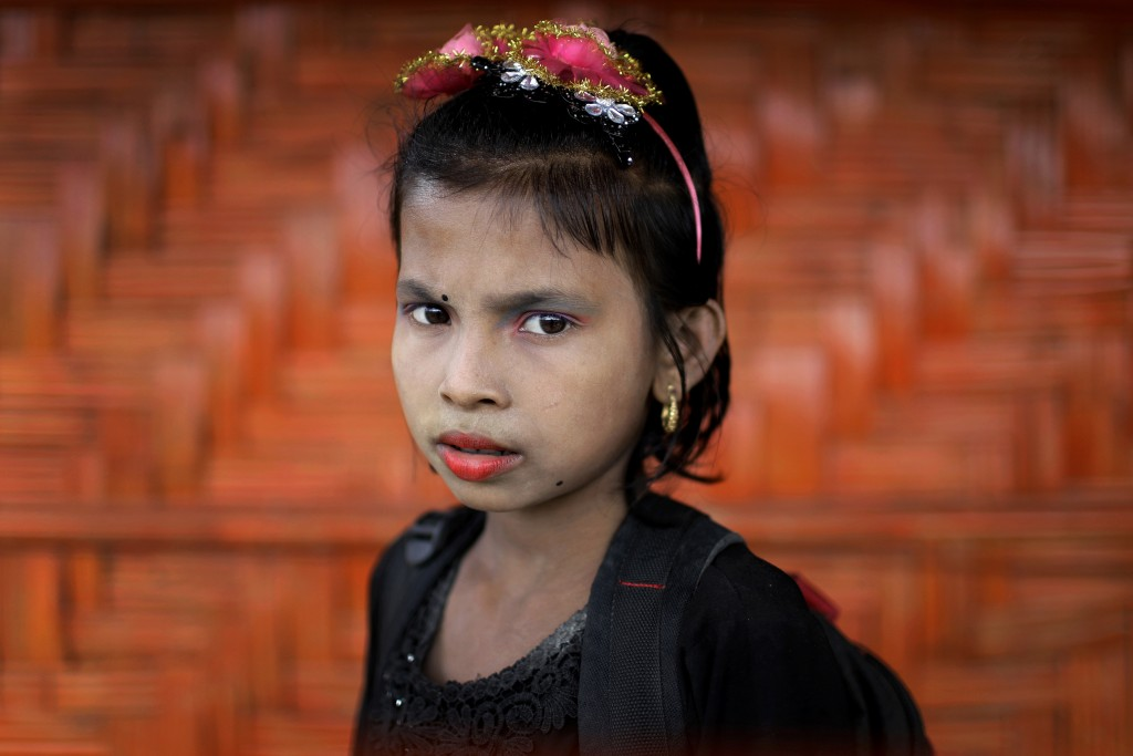 In this June 27, 2018, photo, Ranjeda, 9, poses for a portrait in front of her classroom in Chakmarkul refugee camp, Bangladesh. Amid the misery and m