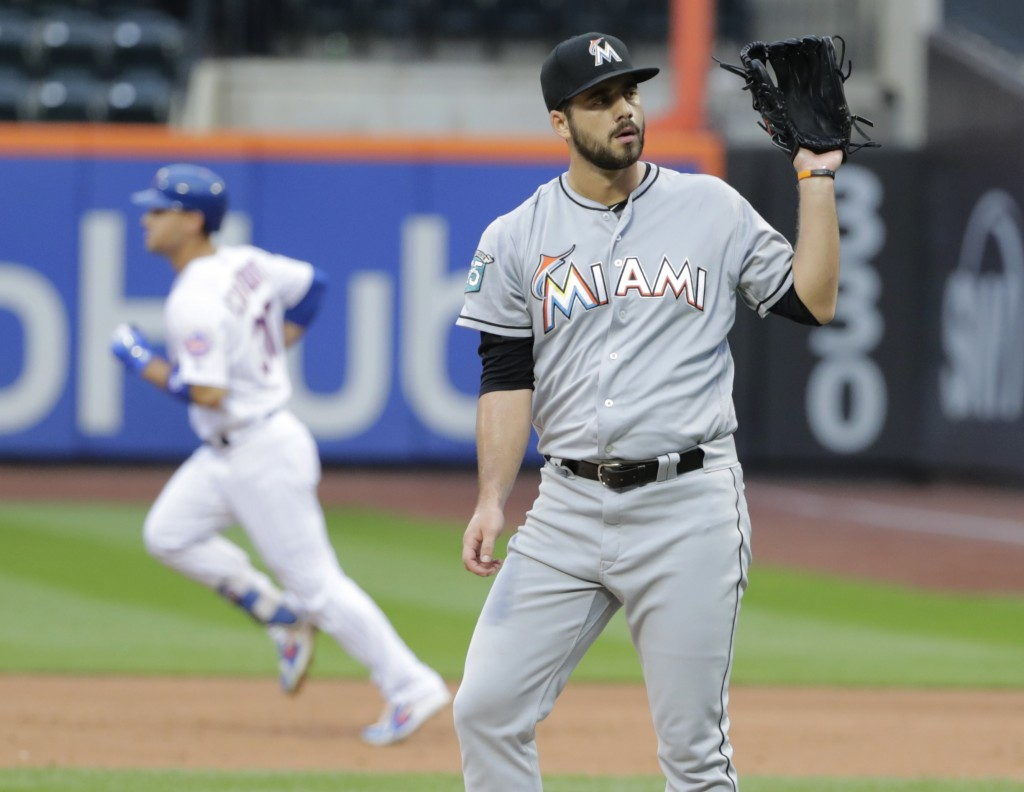 tackles Miami Marlins relief pitcher Kyle Barraclough, right, reacts as New York Mets' Michael Conforto (30) runs the bases after hitting a home run d
