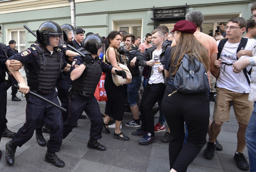 FILE - In this Sunday, Sept. 9, 2018 file photo, police try to block young protesters during a rally protesting retirement age hikes in Moscow, Russia