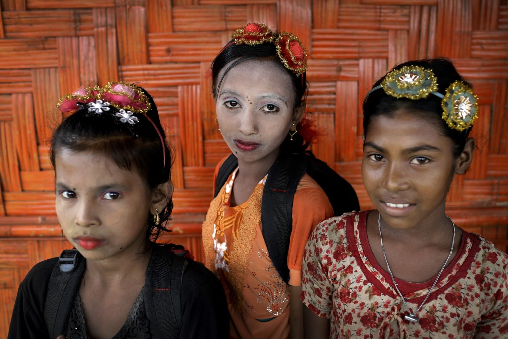In this June 27, 2018, photo, from left, Ranjeda, 9, Rumana, 10, and Zesmin, 10 pose for a portrait in front of their classroom in Chakmarkul refugee
