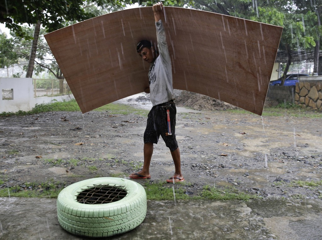 A worker uses a sheet of plywood to cover himself from the rain as Typhoon Mangkhut nears Cagayan province, northeastern Philippines on Friday, Sept. ...