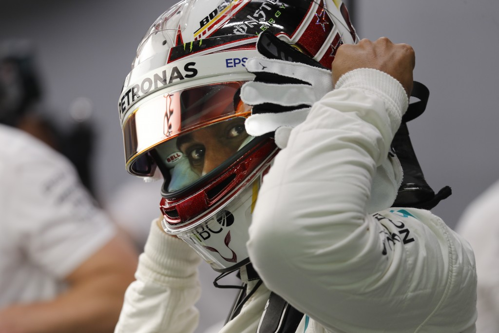 Mercedes driver Lewis Hamilton of Britain waits in his team garage during second practice at the Marina Bay City Circuit ahead of the Singapore Formul...
