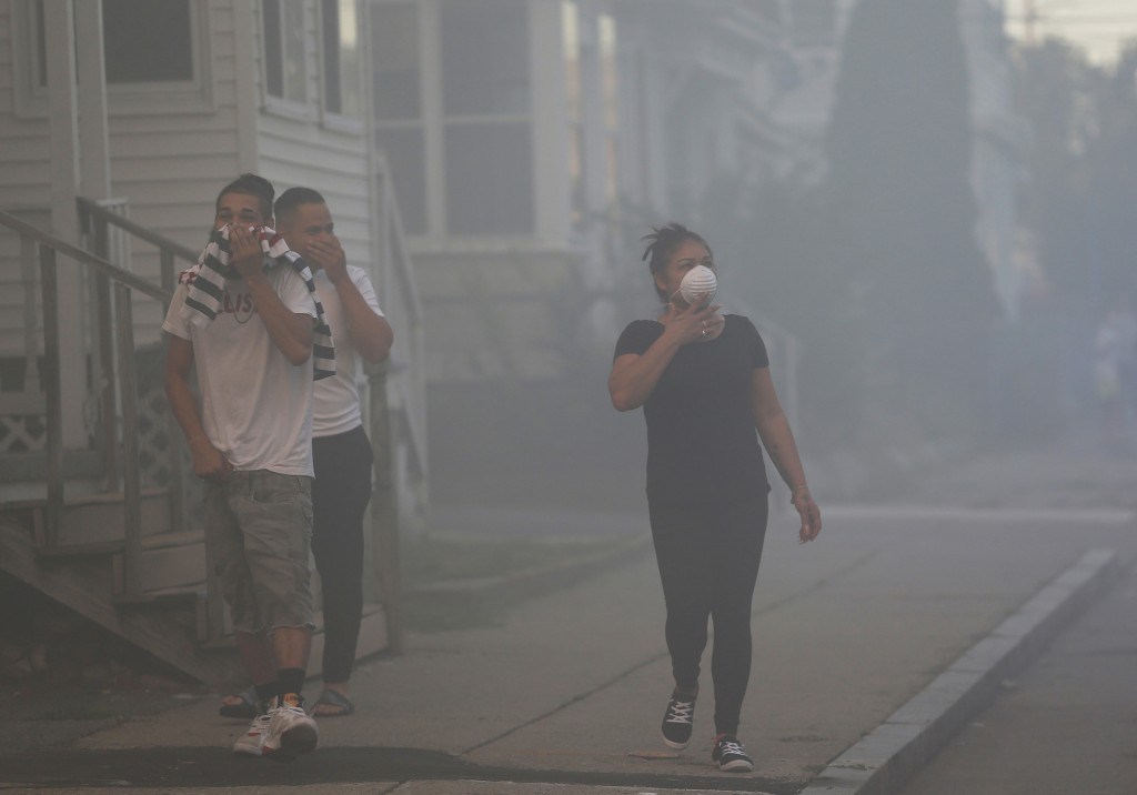 People cover their faces to protect themselves from heavy smoke from a fire on Bowdoin Street in Lawrence, Mass., Thursday, Sept. 13, 2018. The compan