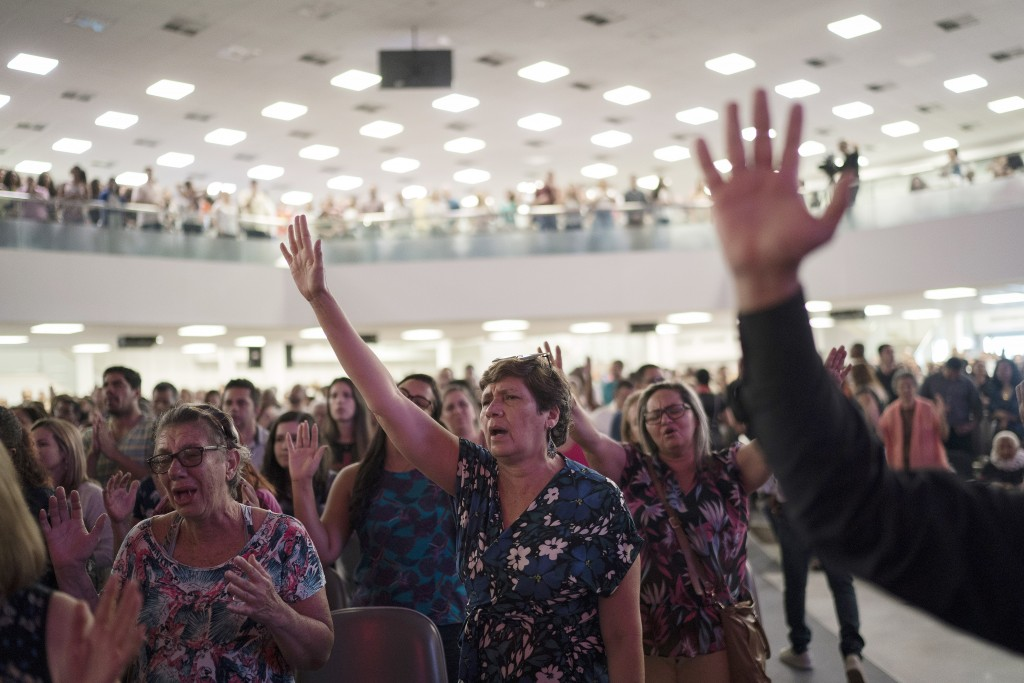 In this Sept. 2, 2018 photo, evangelicals raise their hands in prayer as they listen to a song during a service at the Assembly of God Victory in Chri