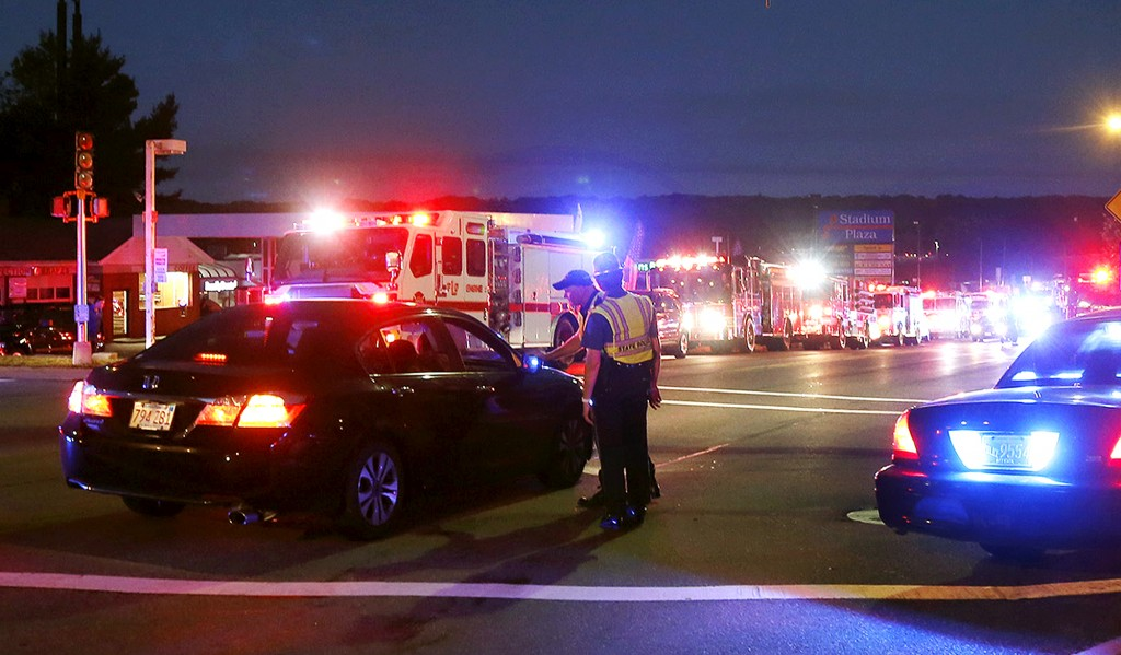 Police officers man a checkpoint as multiple fire trucks from surrounding communities are staged along a road Thursday, Sept. 13, 2018, in Lawrence, M