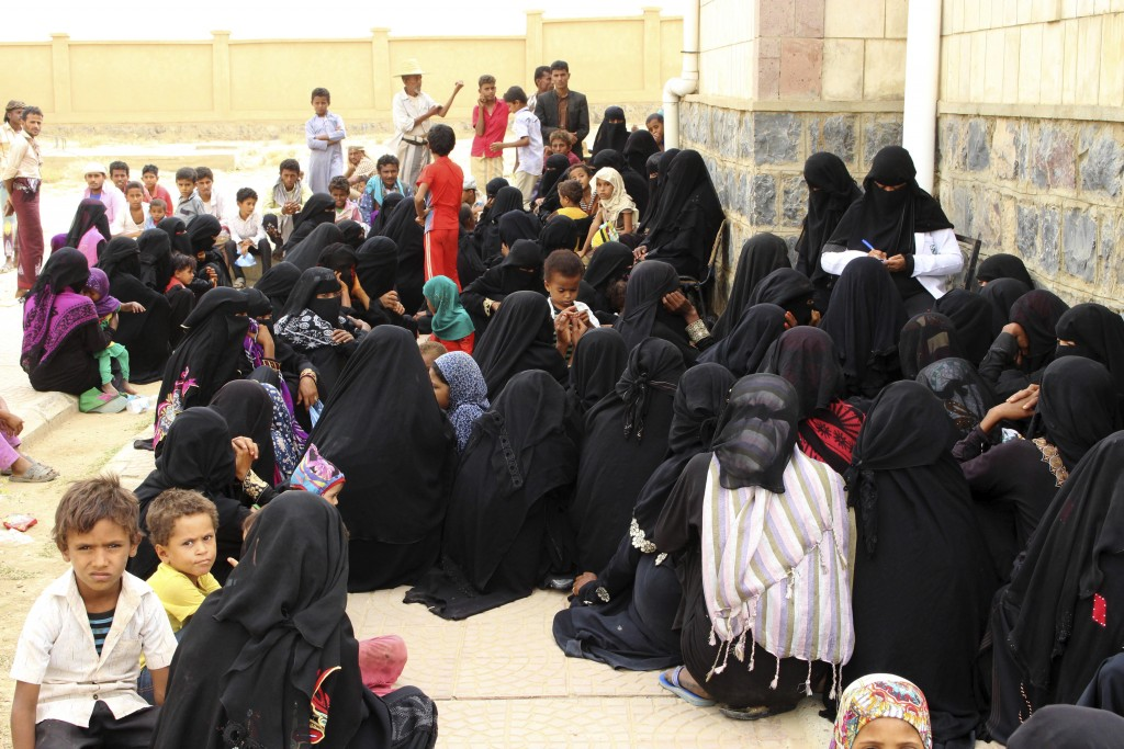 In this Aug. 25, 2018 photo, women wait with their children in front of the Aslam Health Center, in Hajjah, Yemen. Yemenis in the isolated pocket in t