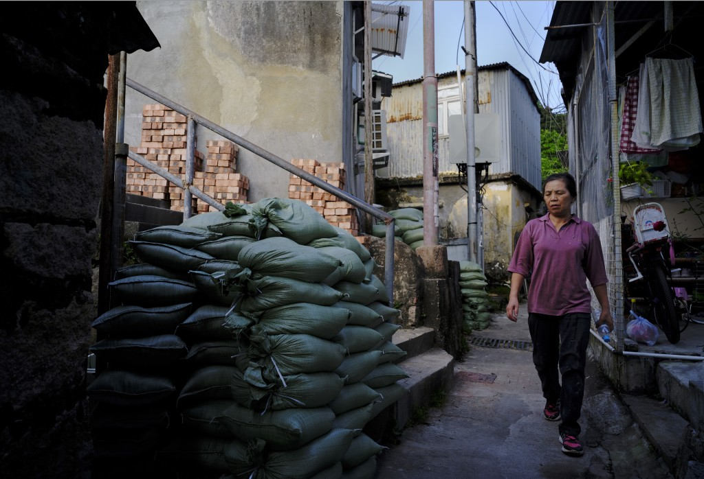A woman walks past sandbags at a village in Lei Yue Mun in preparation for approaching typhoon Mangkhut in Hong Kong Friday, Sept. 14, 2018. The Hong