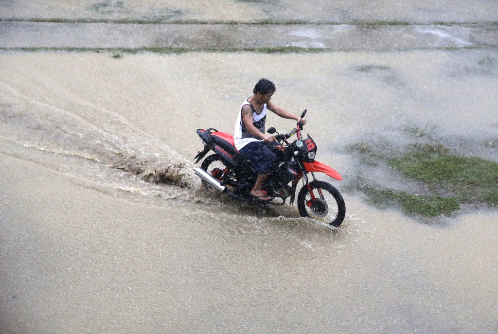 A resident rides his motorcycle across a flooded area as rains from Typhoon Mangkhut begin to affect Tuguegarao city, Cagayan province, northeastern P