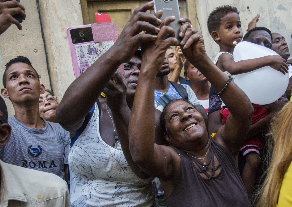 In this Sept. 8, 2018 photo, people take pictures of the annual Virgin of Charity procession in Havana, Cuba. Cuba's patron saint is also recognized a
