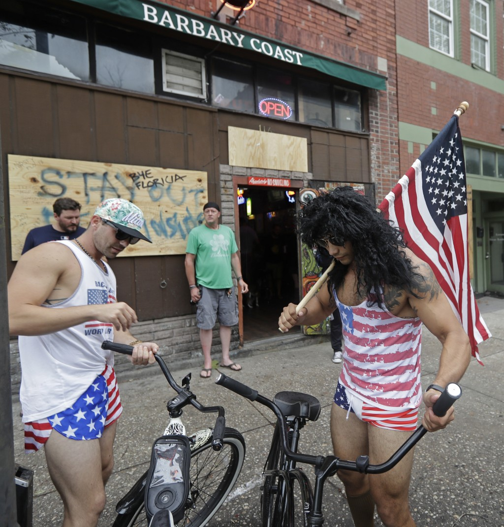 Jeff Egyp, right, and Brandon Fresin, left, park there bikes outside the Barbary Coast bar in downtown Wilmington, N.C., as the Florence threatens the