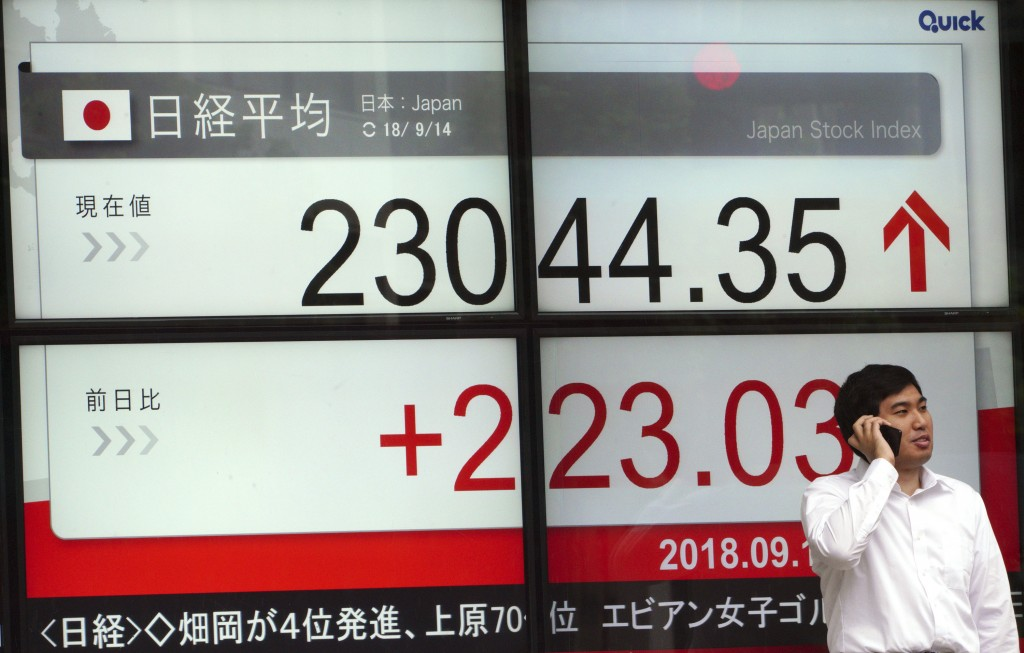 A man stands in front of an electronic stock board showing Japan's Nikkei 225 index at a securities firm in Tokyo Friday, Sept. 14, 2018. Asian shares...