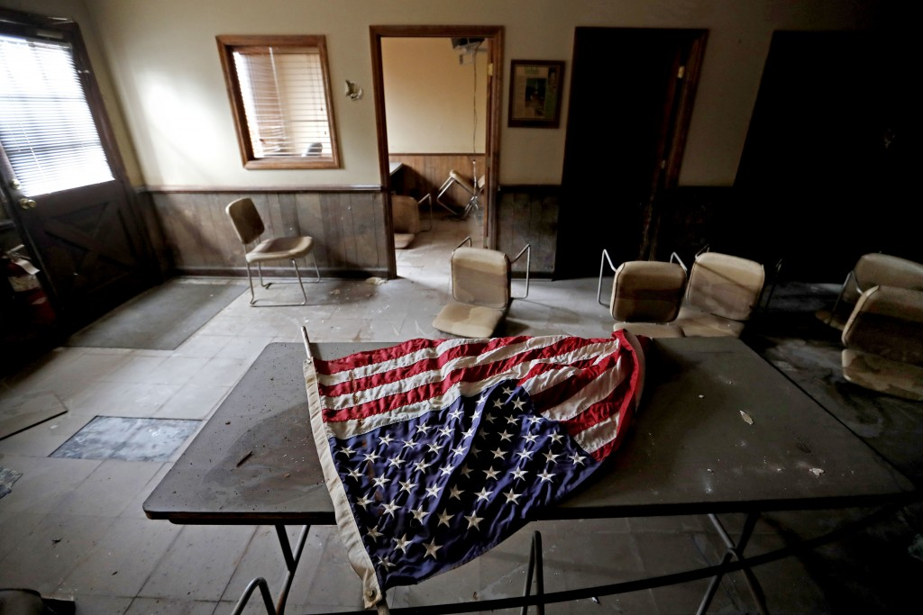 An American flag lays on a table in the old town hall which sits damaged from Hurricane Matthew's flooding two years ago in Nichols, S.C., Thursday, S...