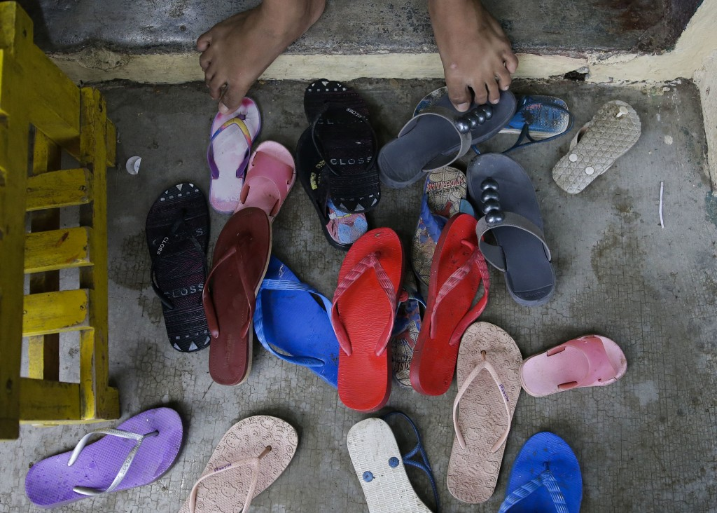 Sandals from evacuees pile outside their room at an evacuation center as rains from Typhoon Mangkhut begin to affect Tuguegarao city, Cagayan province